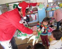 岩手県大槌町、安渡保育所にて。「なにがはいってるのかな?」左は難民を助ける会盛岡事務所の及川亮(2011年12月24日)