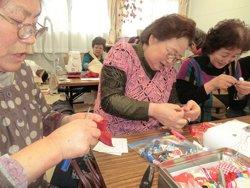 だるま人形を制作する二宮さん(左)と石巻市北上仮設の皆さま(宮城県東松島市内響仮設住宅、2012年3月8日)