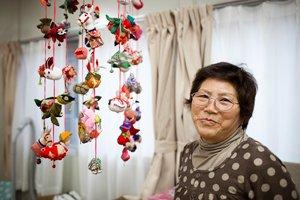 講師を務めてくださった二宮くに子さん。二宮さんの作られたつるし雛の前で(写真提供:GlobalGiving、2012年3月8日)