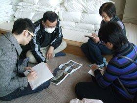 被災地の写真集を見ながら、体験談を聞く留学生ら=花巻市東和町のとうわボランティアの家で