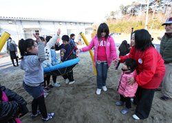 「一緒に乗ろうよ!」上級生の子どもたちが、小さな子にも声をかけていました。右は東京事務局の宮崎佐和子(2012年3月14日、福島県相馬市)