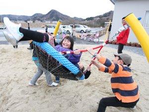 子どもたち3~4人が一緒に乗れるゆりかごスウィング。上級生や大人に大きく揺らしてもらって遊びます(2012年4月13日、福島県相馬市)