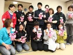 知的・精神障害者通所施設「ひまわりの家」の皆さん。花とサニーちゃんストラップを手に笑顔が咲きました。後列左端は東京事務局の伊藤美洋(2012年4月27日 福島県相馬市)