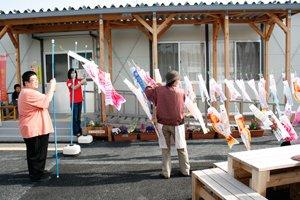 イベント終了後、仮設住宅にお住まいの皆さまのご協力の下、集会所の前にこいのぼりを設置しました(左端は東京事務局の浅野武治。2012年4月29日)