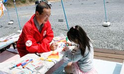 色とりどりの鯉が、子どもたちの手によって次々生まれていきます。左は東京事務局の直江篤志(2012年4月29日)