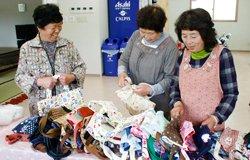 全国の方が丁寧に作ってくださったトートバッグを手にする柚木仮設の方々(2012年4月29日)