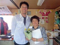 「すぎたさん(左)の歌声がとてもきれいで元気づけられました。花とメッセージも嬉しいです」と阿部るみ子さん。(2012年5月13日 宮城県石巻市)