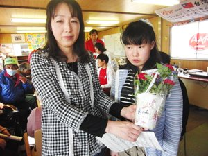 阿部裕子さん(左)は、ミニバラの鉢植えと群馬県の女性からのメッセージ「花からエネルギーをもらって元気になってください」を受け取り、「お花が大好きなので、とても嬉しいです。娘と一緒に大切に育てます。バラは株分けできるので、これから増やしていきたいです」。裕子さんは、震災当時必死で津波から逃れましたが、あと数分逃げるのが遅ければだめだっただろうとのこと。重度の知的障害のある娘の美沙希さん(右)とは何日も連絡が取れなかったそうです。(2012年5月13日 宮城県石巻市)