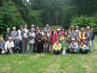 「また、会いましょう」。再会を約束して全員で記念撮影。花束を手にしている人が古川さん=戸塚森森林公園の野外ステージ前で