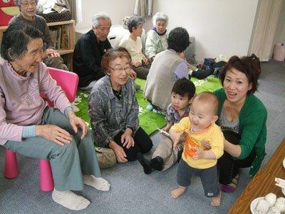 おばあちゃんたちに笑顔を振りまく蒼空ちゃんと母親の美華さん=大槌町の小鎚第5仮設団地で