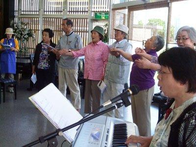 参加者に祝福されながら、照れくさそうに「ここに幸あれ」を歌う坂本さん夫妻(左から4~5人目)=花巻市西宮野目の結海で