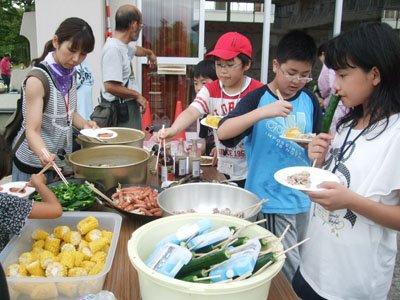 待ちに待った夕食。選り取りみどりのご馳走にみんな歓声。「お肉も野菜も福島じゃ、恐々だもの」とと満面に笑顔=とうわボランティアの家で
