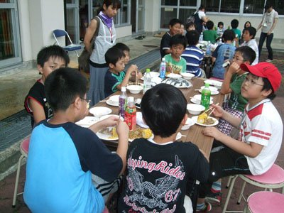 「福島も早く外で自由に遊べるようになればいいなあ」―。野外での食事にみんなご満悦=とうわボランティアの家で