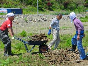 AAR職員も瓦礫や岩の撤去作業を一部お手伝いしました。大きな岩が多く、予想以上に重労働でした。中央は「ふれあい農園」発起人の高橋義弘さん、左は仙台事務所の大原真一郎(宮城県女川町、2012年5月24日)