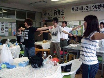 「では行ってきます」。出発前にラジオ体操で体をほぐす学生たち=とうわボランティアの家で