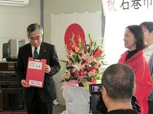 開所式で石巻市長(左)へ歯科診療所の譲渡書を渡すAAR東北事務所長の野際紗綾子(右、2012年6月4日)