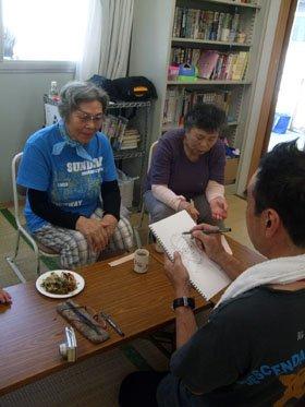 震災体験を語りながら、似顔絵を描いてもらう被災者たち=釜石市鵜住居町日向D仮設団地の談話室で
