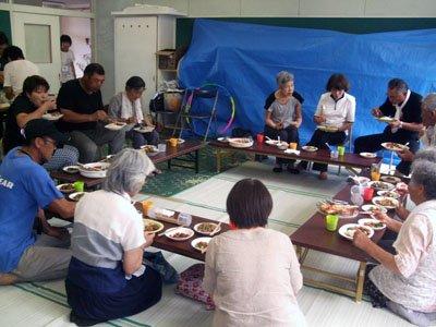 スタッフと談笑しながら、食事をする被災者の人たち=釜石市箱崎町の第3仮設団地に隣接する旧白浜小学校で