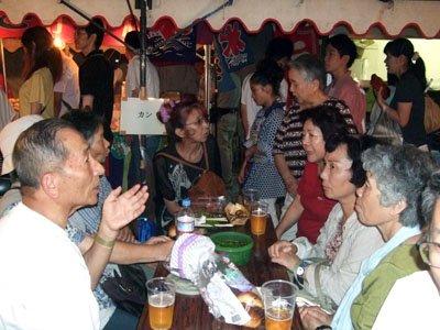「お祭りこそが復興の原点」。花巻祭りを鑑賞しながら、故郷の復興を語り合う被災者。左端はガイドの伊藤さん=花巻市上町で