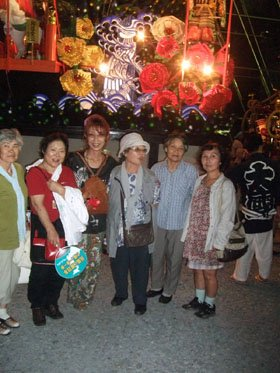 豪華な屋形山車の前で記念写真に収まる被災者の人たち=花巻市上町で