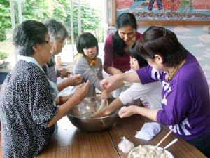 花巻避難者の皆さんが子どもたちにあんころ餅の作り方を指導した=とうわボランティアの家で