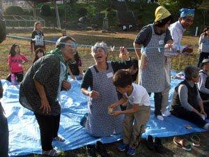 花巻避難者のお年寄りもパン食い競争に挑戦。「子どものころを思い出すなぁ」と懸命に食いついていた=花巻市東和町の旧成島小学校の校庭で