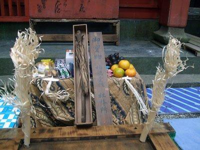 地区住民に初めて開帳された1200年前の「イナウ」。手前の2本は今回のカムイノミのために豊岡さんが持参した=赤崎町尾崎岬の尾崎神社境内で