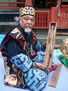 秘宝との約20年ぶりの再会に豊岡さんも少し緊張気味だった=赤崎町尾崎岬の尾崎神社境内で