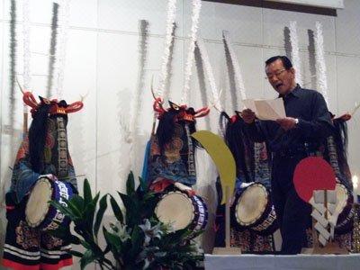 鹿(しし)踊りの鎮魂の舞をバックに「ばあさんのせなか」を朗読する照井さん=2012年3月11日、震災1周年の追悼行事で(花巻市のなはんプラザ)