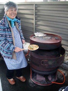 焼きあがったピザを手に喜ぶ被災者の佐々木好子さん=花巻市御田屋町の厚生病院跡地で