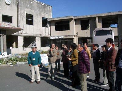 参加者たちは無残な姿をさらけ出す、旧大槌町役場の庁舎前で絶句した=大槌町内で