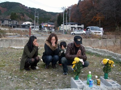 土台を残すだけの住居跡に花を捧げ、孫たちと一緒に手を合わせる白銀さん(右)=大槌町安渡で