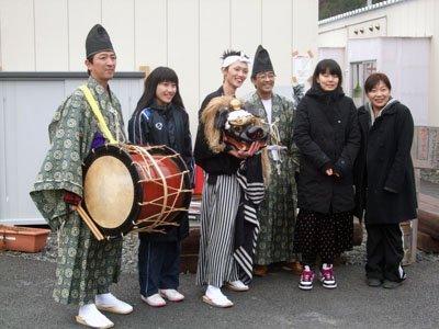 神楽衆やボランティアの高校生と一緒に記念写真に納まる笹原さん(右)=大槌町大槌の第10仮設団地の広場で