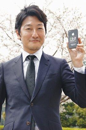 J-CASTニュースの取材に答えた堀潤さん(3月29日、都内で)。手にしているのは「8bit News」のロゴ入りスマートフォン