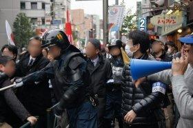 抗議活動側(右)の発言に、デモ参加者(左)がつかみかかろうとするも、警官に制止される