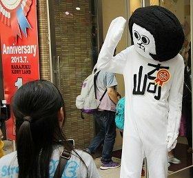 8月7日、東京・原宿で撮影会に登場したオカザえもん。手前の少女も熱心に写真を撮影していた