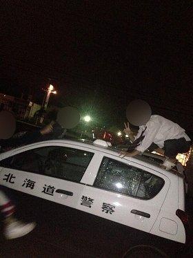 25日に発覚した、「バカッター」写真の一例。パトカーの車上で悪ふざけをする若者たち。すでに警察が捜査を開始している