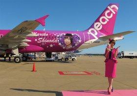 ピーチ成田初便の「MARIKO JET」を背にする篠田麻里子さん