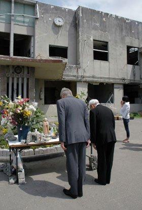 旧大槌町役場庁舎の前で犠牲者の霊を慰める人たち=2013年7月2日