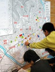 湧水地点に測定結果を色別で示したシールを貼る参加者=2013年5月19日、大槌町役場の多目的会議室