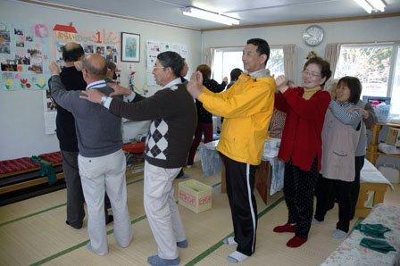 体操の最後に互いに肩をたたき合う住民たち=2013年4月12日、大鎚町柾内の「大槌仮設団地」