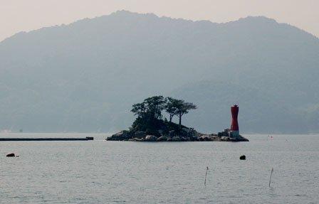 防波堤造りが進む蓬莱島。完成すれば徒歩で島に渡ることができる=2013年8月11日、大槌湾