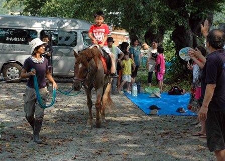子どもたちは馬に触れたり乗ったりして楽しんだ=2013年8月17日、大槌町の旧赤浜小校庭