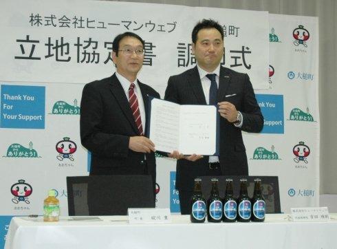 立地協定書に調印したヒューマンウェブの吉田琇則社長(右)と碇川豊大槌町長(左)=2013年10月9日、大槌町役場