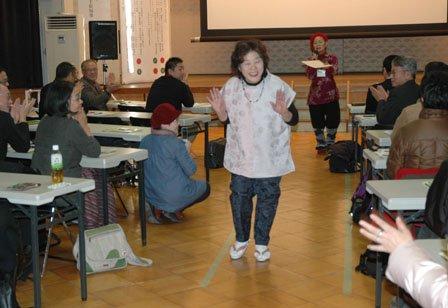 和服から仕立て直した洋服を着て観客席を歩くお年寄りのモデル=2013年12月1日、大槌町中央公民館