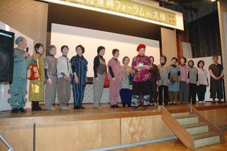 舞台に勢ぞろいした仮設住宅に住むモデルの人たち。中央が小赤澤直子さん=2013年12月1日、大槌町中央公民館