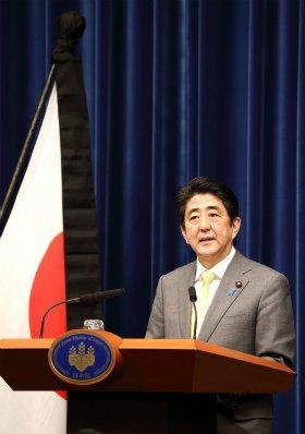記者会見に臨む安倍晋三首相。国旗には喪章がついている