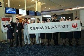 JALの初便はロンドン行き。横断幕で見送った(左から2番目が植木義晴社長)