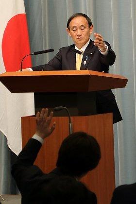 会見で挙手する記者を指名する菅義偉官房長官(奥)