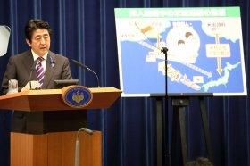 記者会見に臨む安倍晋三首相。「邦人輸送中の米輸送艦の防護」と題したパネルを使いながら閣議決定の正当性を強調した